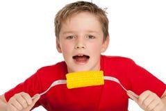 吃玉米棒子的英俊的年轻男孩。 免版税库存照片