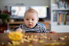 吃玉米片和微笑的逗人喜爱的矮小的小孩男孩 库存图片