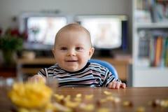 吃玉米片和微笑的逗人喜爱的矮小的小孩男孩 库存照片