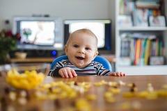 吃玉米片和微笑的逗人喜爱的矮小的小孩男孩 免版税库存照片
