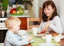 吃玉米片和面包早餐膳食的家庭在桌上 库存图片