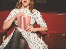 吃玉米花和观看电影的妇女 免版税库存图片