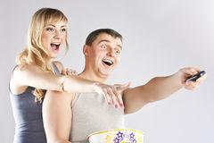 吃玉米花电视注意的年轻人的夫妇 免版税库存图片