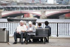 吃玉米花的一对年长夫妇,坐俯视泰晤士的长凳 泰晤士的南岸 免版税库存照片