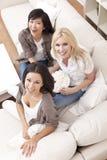 吃玉米花的三个美丽的妇女朋友 图库摄影