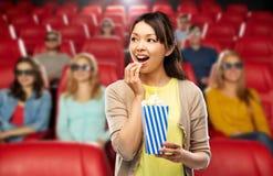 吃玉米花的亚裔妇女在电影院 免版税库存照片