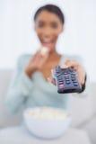 吃玉米花的可爱的妇女,当看电视时 免版税库存图片