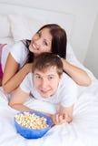 吃玉米花的夫妇 免版税图库摄影