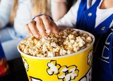 吃玉米花的女孩在戏院剧院 免版税库存图片