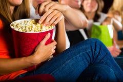 吃玉米花的女孩在戏院或电影院 图库摄影