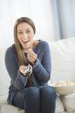 吃玉米花的妇女,当看电视时 免版税库存照片