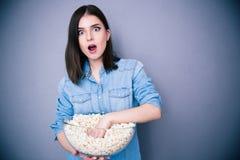 吃玉米花的惊奇俏丽的妇女 免版税库存照片