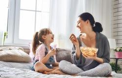 吃玉米花的母亲和女儿 免版税库存照片