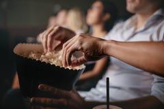吃玉米花的青年人在电影院 免版税库存照片