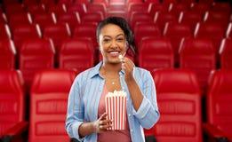 吃玉米花的非洲妇女在电影院 免版税库存图片