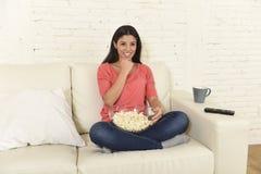 吃玉米花观看的电视的愉快的妇女在沙发长沙发愉快的激动的享用的电影 库存图片