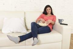 吃玉米花观看的电视的愉快的妇女在沙发长沙发愉快的激动的享用的电影 免版税库存照片