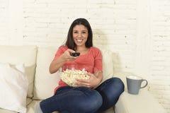 吃玉米花观看的电视的愉快的妇女在沙发长沙发愉快的激动的享用的电影 免版税库存图片