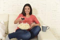 吃玉米花观看的电视的愉快的妇女在沙发长沙发愉快的激动的享用的电影 库存照片
