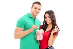 吃玉米花年轻人的夫妇 图库摄影