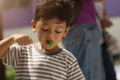 吃球被镀的点心的亚裔男孩 库存照片