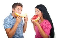 吃瓜年轻人的夫妇 免版税库存照片