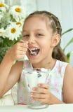 吃甜点心用莓果的女孩 图库摄影