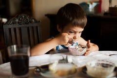 吃甜点的疲乏的孩子 免版税图库摄影