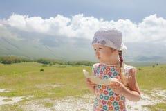 吃甜瓜切享受高山看法的小女孩 库存图片