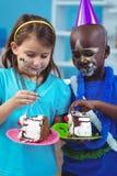 吃生日蛋糕的愉快的孩子 免版税图库摄影
