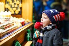 吃番荔枝甜点的小孩男孩在圣诞节市场上站立 库存照片