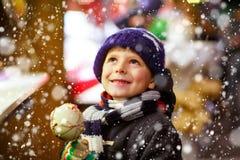 吃番荔枝甜点的小孩男孩在圣诞节市场上站立 免版税库存图片