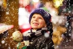 吃番荔枝甜点的小孩男孩在圣诞节市场上站立 免版税库存照片