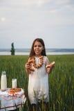 吃百吉卷用在绿色领域,夏令时的牛奶的逗人喜爱的微笑的小女孩 免版税图库摄影