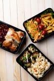 吃的准备好膳食在木桌,豆沙,被烘烤的鸡翅,茄子,夏南瓜上 免版税库存照片