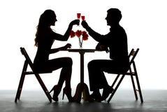 吃的夫妇与酒杯的晚餐在表上 库存照片