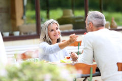 吃的夫妇午餐在晴天 免版税库存图片