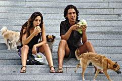 吃的夫妇,当坐台阶时 免版税库存照片