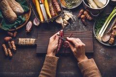 吃的菜烹调和 在黑暗的土气厨房用桌背景的妇女女性手削皮红萝卜与各种各样的根vegetab 免版税库存图片