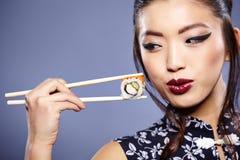 吃眼睛的美好的深度调遣重点浅寿司妇女年轻人 免版税库存照片