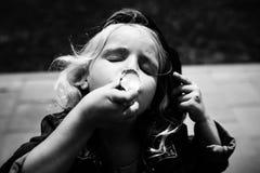 吃着冰淇凌的愉快的女孩 儿童` s乐趣 免版税库存照片