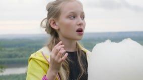 吃着甜棉花走在城市公园的青少年的女孩画象  股票录像