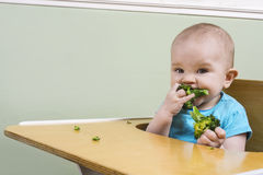 吃硬花甘蓝的滑稽的婴孩 免版税图库摄影