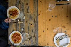 吃简单的便宜的膳食木表的人们户外 库存图片