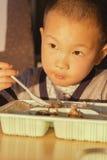 吃箱子午餐的男孩 免版税库存照片