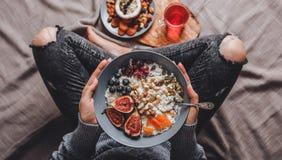 吃米椰子粥用无花果、莓果、坚果和椰奶的妇女在板材 健康早餐成份 免版税库存图片