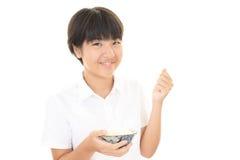 吃米的女孩 免版税库存图片