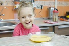 吃粥的女孩在厨房里 免版税库存图片