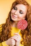 吃糖果棒棒糖的年轻女人 免版税库存图片