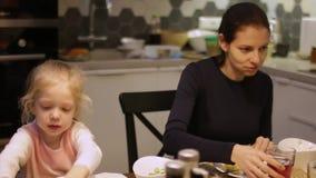 吃系列父亲母亲薄饼的大儿童正餐 妈妈和女儿吃着 股票录像